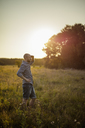 Man standing in grassy field at sunset - FOLF05917