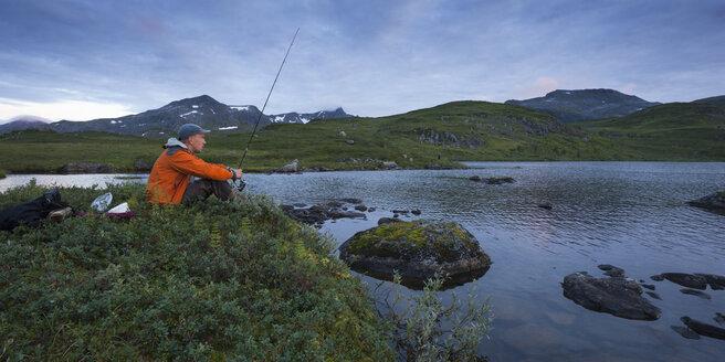 Man fishing in lake Sjuendevatnet at dusk - FOLF05920