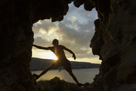 Silhouette man climbing rock formation against sky during sunset - CAVF31617