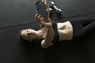 High angle view of woman taking selfie while lying on floor at gym - CAVF31629