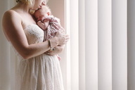 Mother carrying daughter while standing by window at home - CAVF31641