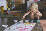 Shirtless boy with watercolor paints making apple prints on white paper at home - CAVF31653