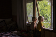 Brothers looking through window while standing at home - CAVF31656