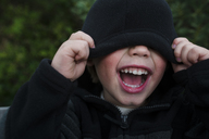 Boy screaming while covering eyes with hooded shirt - CAVF31659