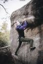 Full length of woman rock climbing - CAVF31737