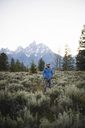Hiker with hands in pockets standing on field against mountains and clear sky at Grand Teton National Park - CAVF31761