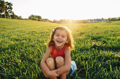 Portrait of happy girl on grassy field at park - CAVF31782