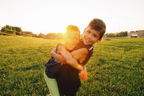 Portrait of playful boy lifting brother on field at park during sunset - CAVF31785