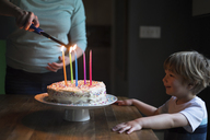 Excited boy looking at woman lightning colorful candles on birthday cake - CAVF31815