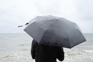 Woman under black umbrella watching Baltic Sea - FOLF06014