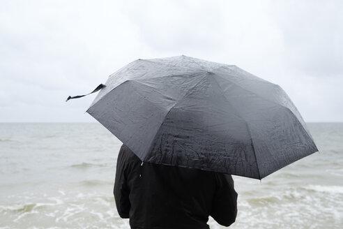 Woman under black umbrella watching Baltic Sea - FOLF06014