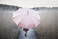 Woman with umbrella walking on wooden pier - FOLF06185