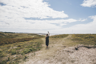 France, Brittany, Landeda, Dunes de Sainte-Marguerite, young woman walking on dune at the coast holding cell phone - GUSF00580