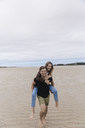 France, Brittany, Guisseny, happy young man carrying girlfriend piggyback on the beach - GUSF00586