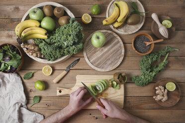 Man preparing green smoothie slicing kiwi - RTBF01122