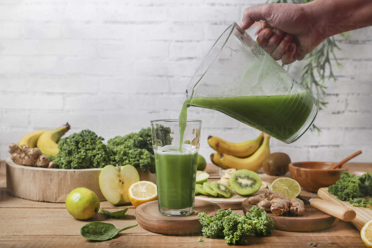 Man serving glass of green smoothie surrounded by ingredients - RTBF01125 - Retales Botijero/Westend61