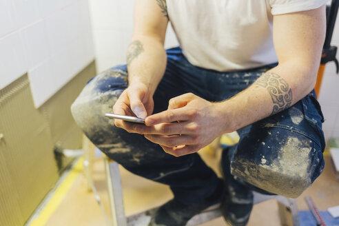 Tiler holding a smart phone - FOLF06246