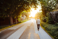 Man walking on road at sunset - FOLF06372