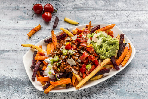 Vegetable fries with vegetarian bolognese, guacamole, yogurt dip, tomatoes, spring onions and parmesan on plate - SARF03639