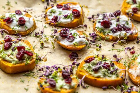 Slices of sweet potato with cream cheese, ramson cream, goat cheese, cress and cranberries - SARF03645