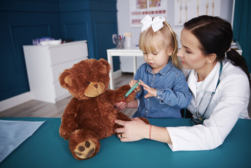 Doctor and girl vaccinating teddy in medical practice - ABIF00219