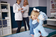 Girl hugging teddy in medical practice with doctor and mother in background - ABIF00225