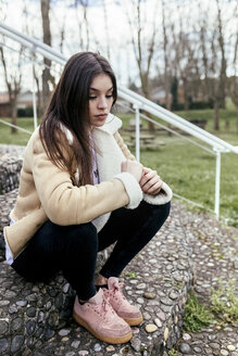 Serious young woman sitting outdoors on steps - MGOF03743
