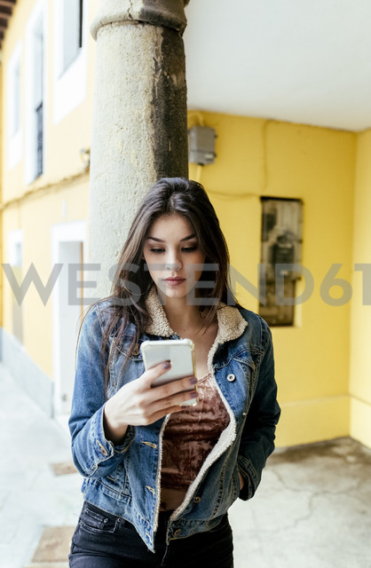Young woman in a town checking her smartphone - MGOF03752 - Marco Govel/Westend61