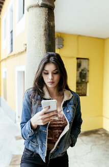 Young woman in a town checking her smartphone - MGOF03752