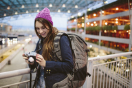 Smiling woman with backpack looking at camera while leaning on railing in airport - CAVF32122