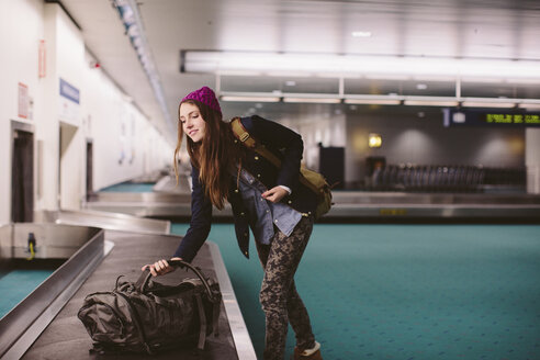 Woman carrying luggage from baggage claim at airport - CAVF32125