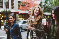 Cheerful female friends having coffee while walking on city street - CAVF32143