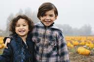 Portrait of happy brothers standing at pumpkin patch during foggy weather - CAVF32179