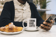 Close-up of man with croissant and cup of coffee in a cafe using cell phone - MAUF01360