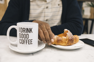 Close-up of man with croissant and cup of coffee in a cafe - MAUF01363