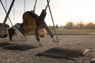 Portrait of happy boy leaning upside down on swing at playground - CAVF32378