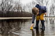 Boy playing with rubber duck in puddle - CAVF32381