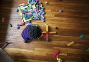Overhead view of boy playing with toy blocks on hardwood floor at home - CAVF32672