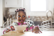 Cute girl making face while having breakfast in kitchen - CAVF32675