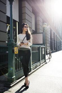 Full length of woman looking away while listening music on sidewalk - CAVF32768