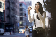 Happy woman photographing through smart phone in city - CAVF32777