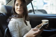 Young woman holding disposable glass and smart phone in taxi - CAVF32795