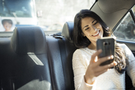 Happy young woman taking selfie through smart phone in taxi - CAVF32801