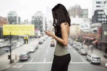 Side view of woman using smart phone by glass window with city street in background - CAVF32828