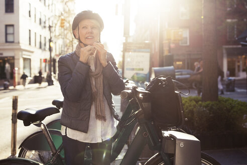 Thoughtful senior woman wearing helmet while standing by bicycles - CAVF32897
