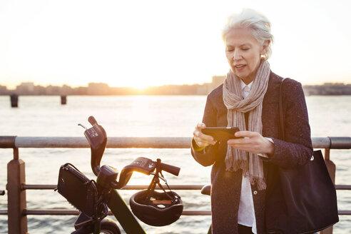 Senior woman using smart phone by bicycle against sea - CAVF32906