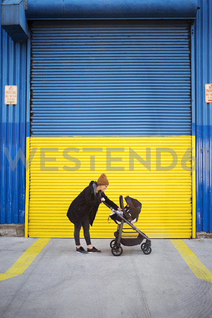 Side view of woman with baby carriage on street - CAVF32915 - Cavan Images/Westend61