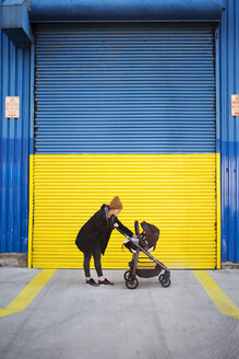 Side view of woman with baby carriage on street - CAVF32915