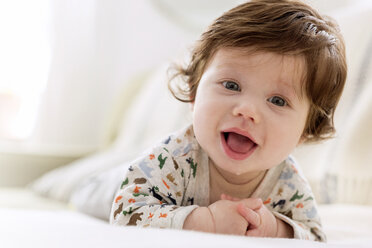 Close-up portrait of cute baby boy lying on bed at home - CAVF32921