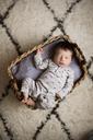 Overhead view of baby boy sleeping in basket on rug at home - CAVF32924
